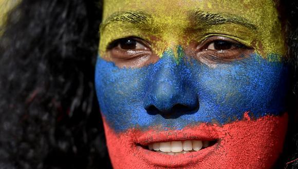 Una mujer con el rostro pintado con los colores de la bandera colombiana participa en una protesta  en Cali, Colombia. (Foto de Luis ROBAYO / AFP).