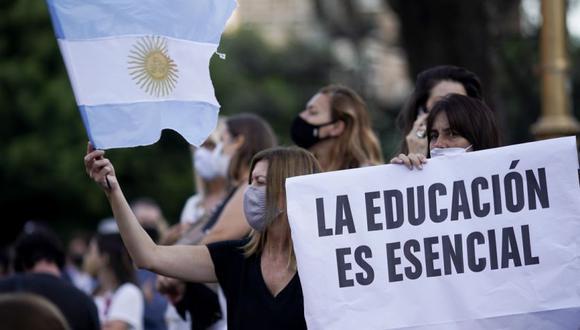 """Una mujer sostiene el cartel: """"La educación es esencial"""" durante una protesta frente al Ministerio de Educación luego de que el gobierno decidiera suspender las clases presenciales para frenar un aumento en los casos de coronavirus en Buenos Aires, Argentina. (Foto: AP / Víctor R. Caivano)."""