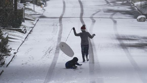 Los niños juegan con un trineo mientras la nieve comienza a acumularse en San Antonio. La nieve, el hielo y el clima bajo cero continúan causando estragos en la red eléctrica y los servicios públicos del estado. (Foto: AP / Eric Gay).